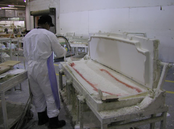 person using AcraStrip to safely clean a component in a factory